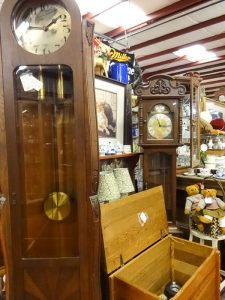 Two grandfather clocks in picture, one in a sleek rounded top, the other with ornate carved top