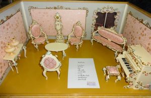Miniature Victorian pink dollhouse room setting in pink, includes settee, chairs, side tables, piano and bench, clock, and lamps ,Showcase 18