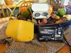 Bright yellow LV pochette, black leather organizer and sunglasses
