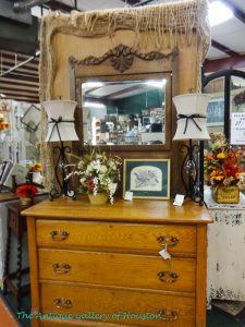 Three drawer chest, mirror, two small lamps and floral arrangement