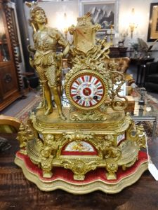 Mantle clock, gold with red highlights, militiaman or nobleman on left
