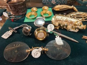 Assortment of gold and silver vintage or vintage-inspired jewelry pieces, pair of round spectacles, and a gold secret box in the shape of a pig