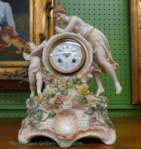 Porcelain clock with cherub and nymph figurines in off-white with green and yellow flowers