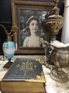 Grouping of antique items such as a portrait, vase, urn, and Bible, Booth A 6