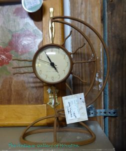 Rustic sun-motif clock hanging from stand