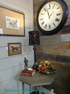 Corner grouping with table, lamp, and large wall clock, Booth T2