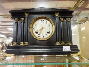Mantel or tabletop clock, columns on either side of clock, black wood with gold tones