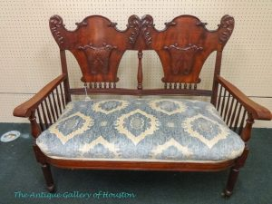 Love seat with ornate carved back and spindle arms, upholstered seat in pale blue and white, Booth L2