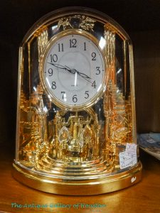Table top ornate gold clock under glass dome