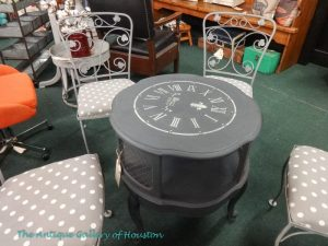 Four metal chairs in gray, upholstered in gray and white polka dots, with center repainted table with clock face on top, Booth R 4a