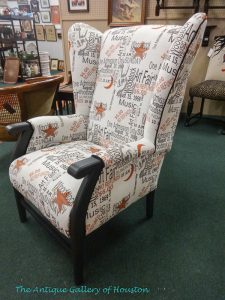 High back, armed chair upholstered in white fabric with blue and red lettering, phrases are Woodstock era lingo, Booth T5