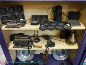 Variety of cast iron kitchenware pieces, Booth V7