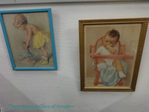 Framed pictures of baby in high chair and toddler with doll, Booth V7