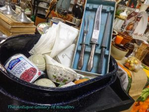 Holiday dinner supplies, roasting pan, carving knives, linens, and gravy boat, Booth W 8
