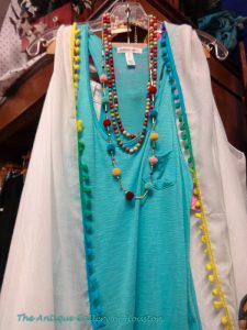 Turquoise t-shirt and white beach wrap with multi-color trim, accented with strands of colorful beads, Booth X 7