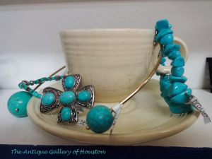 Cream colored Fiesta teacup and saucer surrounded by turquoise colored stone jewelry, Booth X 7