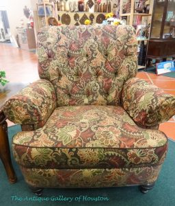 Large upholstered overstuffed armchair in big paisley print of greens and maroon, Booth S1